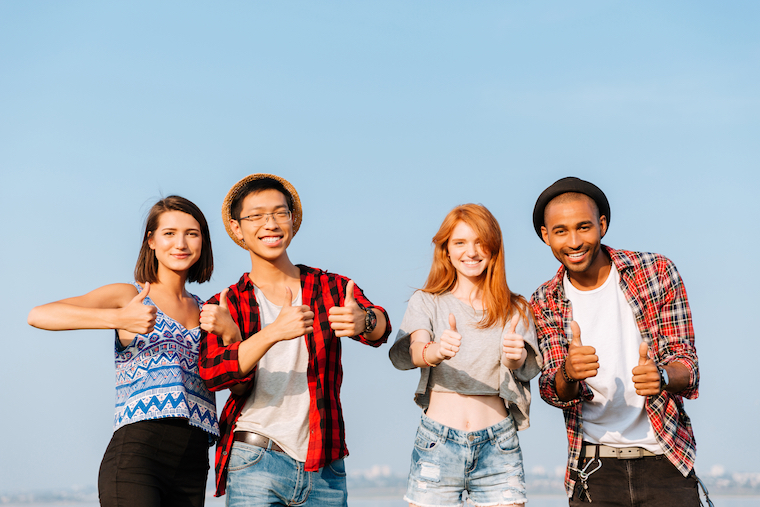Multiethnic group of smiling friends standing and showing thumbs up
